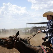 La Vaquera, cowgirl at Galisteo Rodeo, New Mexico. Female barrel racing, action shot.
