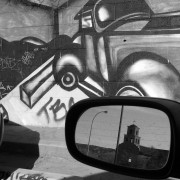 Black and white photography, side mirror reflection of Guadalupe Church, Santa Fe, NM. NM Department of labor parking lot, wall mural art.