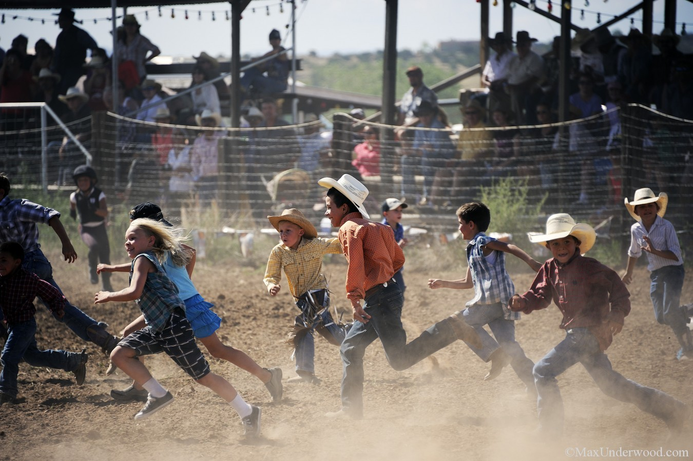 Kids running at Galisteo Rodeo, New Mexico, calf chasing, children at play